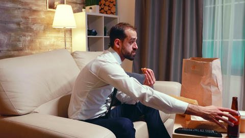 Side view of businessman eating junk food and drinking beer Live Action