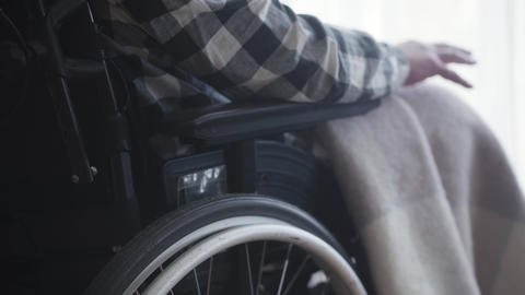 Close-up of wheelchair with disabled old Caucasian man sitting in it. Mature Live Action