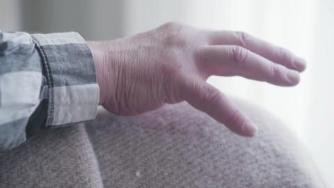 Extreme close-up of old male Caucasian hand on knees covered with blanket Live Action
