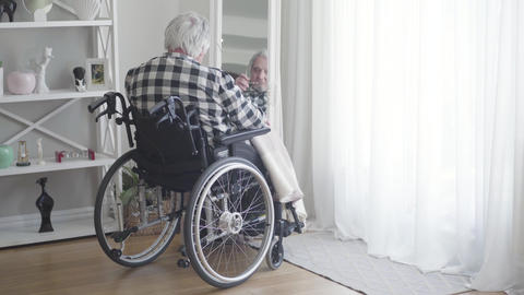 Back view of mature Caucasian man in wheelchair looking at his reflection in Live Action