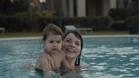 Mother and baby girl enjoying vacation poolside Live Action