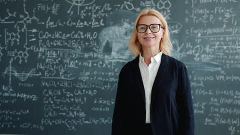 Slow motion of friendly teacher smiling looking at camera standing alone in Live Action