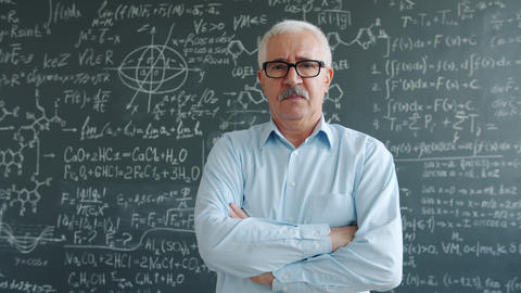 Serious scientist standing indoors with arms crossed near chalkboard with Live Action