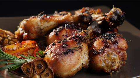Rotating grilled chicken legs on a plate Live Action
