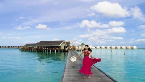 Woman dances in front of an ocean villa Live Action