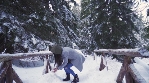 Brunette girl throwing handful of snow in the air, having fun in snow day Live Action
