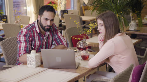 Portrait of young Caucasian woman and Middle Eastern man having business lunch Live Action