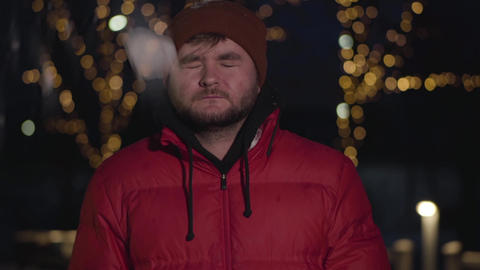 Young bearded Caucasian man getting snowball in face, opening grey eyes and Live Action