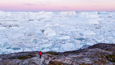 Travel in arctic landscape nature with icebergs - Greenland tourist man explorer Live Action