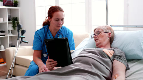 Old woman lying in bed learning from female doctor to use tablet computer Live Action