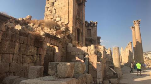 Jerash, Jordan - October 15, 2019: tourists inspect the ruins of old buildings Live Action