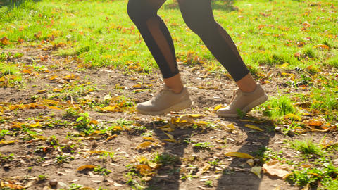 4k slow motion video of young sporty woman running in the autumn park against Live Action