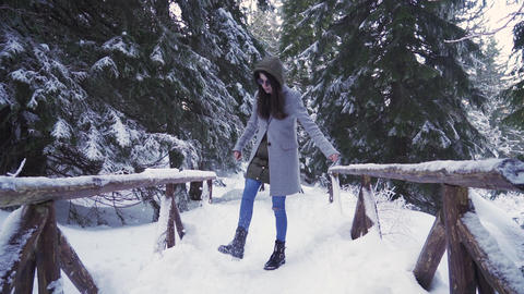 Woman in gray coat kicking snow and having fun during holiday in the forest ライブ動画