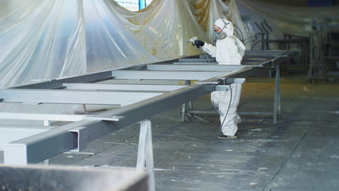 worker in mask with sprayer paints carcass in workshop Live Action