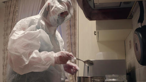 Infected woman in protective suit cooking on home kitchen. Woman in white Live Action