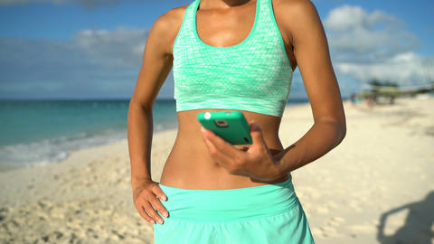Beach runner woman showing touchscreen on smartphone for running fitness app Live Action