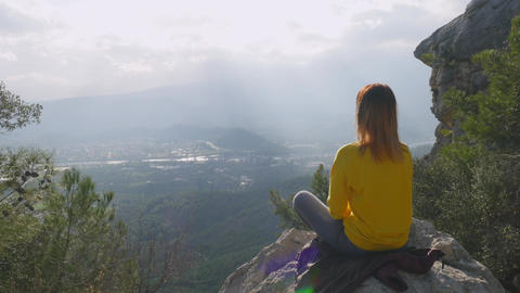 Young woman sitting in yoga pose on the end of the cliff ライブ動画