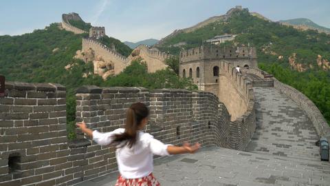 Happy cheerful joyful tourist woman at Great Wall of China having fun travel Live Action
