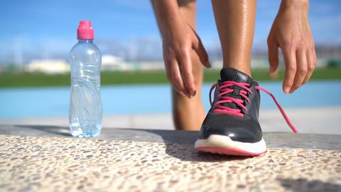Sports woman runner getting ready for run tying running shoes with water bottle Live Action