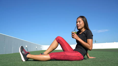 Healthy Asian woman runner drinking green smoothie before fitness exercise Live Action