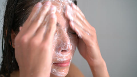 Skincare woman washing face with facewash soap in shower ライブ動画