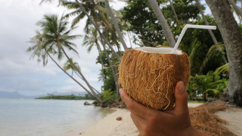 Coconut water drink on paradise beach - vacation woman holding coconut Live Action