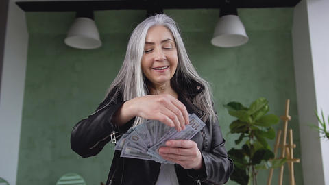 Close up of happy beautiful rich mature woman with gray hair which holding Live Action