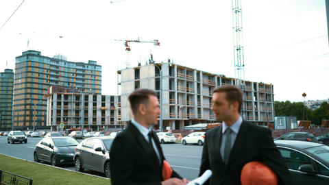 Two architect discuss new building and make handshake Live Action