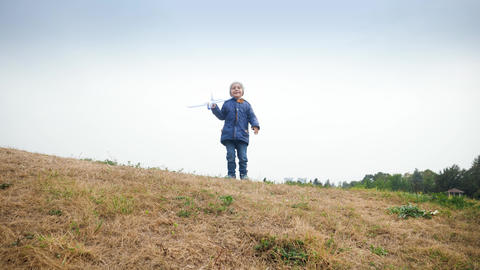 4k video of cheerful smiling and laughing little boy standing on high hill and Live Action