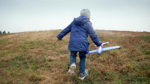 4k video of cheerful little boy holding toy airplane and running on the hill top Live Action