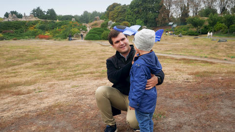 4k video of happy cheerful young father launching toy airplane at the park Live Action