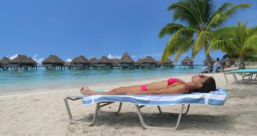 Vacation beach travel suntanning young woman on relaxing on beach in bikini Live Action