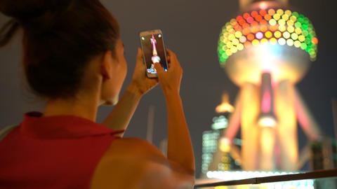 Shanghai China travel tourist taking photo with smart phone of Oriental Pearl Live Action