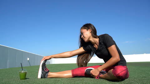 Seated one-legged toe touch woman stretching on outdoor fitness gym grass Live Action