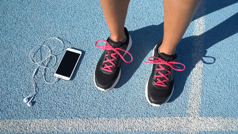 Running shoes woman holding smartphone and earphones for music motivation Live Action
