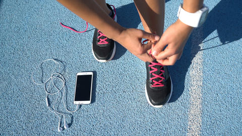Runner getting ready tying running shoes with smartwatch earphones and phone Live Action