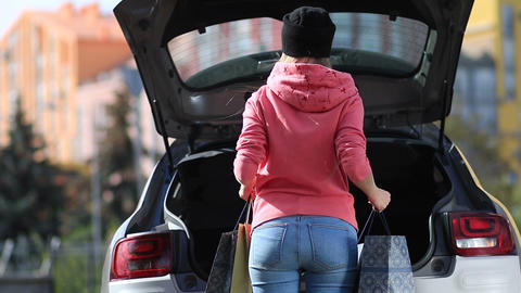 Back view of woman putting shopping bags in car Footage