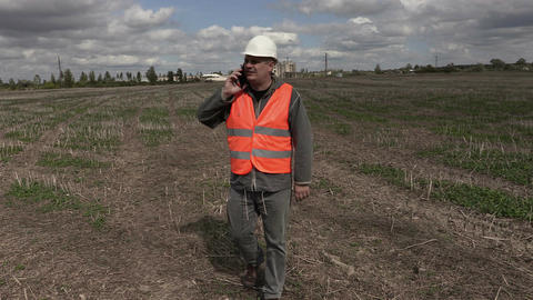 Engineer talking on the smartphone and walking on the field near factory Footage