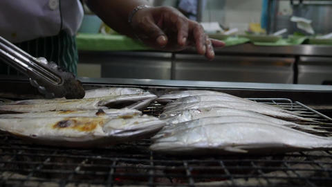 The cook makes grill fish and shrimp. Cooking mackerel fillet at grill for fish Live Action