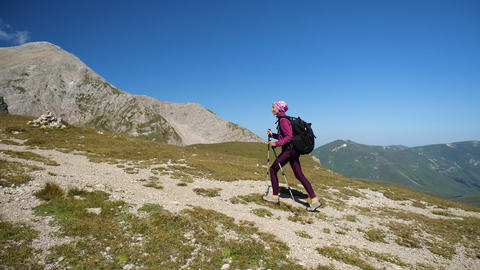 Young woman Nordic walking in the mountains, fitness and exercise outdoors. Girl Live Action