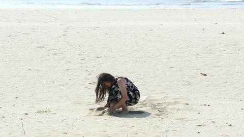 Girl covers sandals with sand at beach Live Action