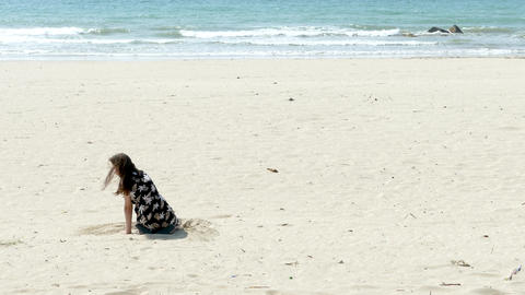 Girl look at camera and plays in sand Live Action
