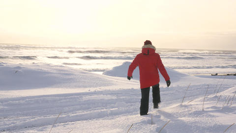 A young man walks along the coast of the Pacific ocean in winter 006 Live Action