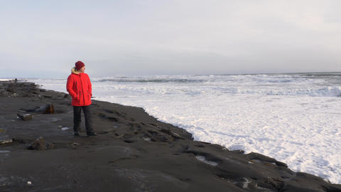 A young man walks along the coast of the Pacific ocean in winter 015 Live Action