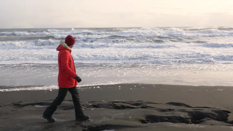 A young man walks along the coast of the Pacific ocean in winter 013 Live Action
