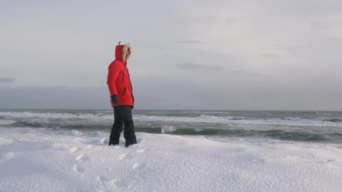 A young man walks along the coast of the Pacific ocean in winter 016 Live Action