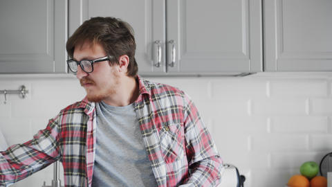 Young man using phone and drinking coffee while sandng in the kitchen GIF
