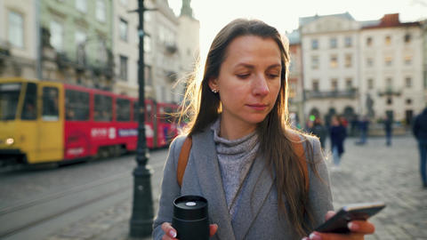 Woman with a thermos cup in hand walking down an old street using smartphone at Live Action