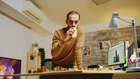 Tired architect taking a sip of coffee while working on a building project GIF