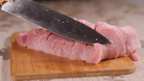 Draw a metal blade through the flesh. Pork is on the Board. Sliced pork meat Live Action